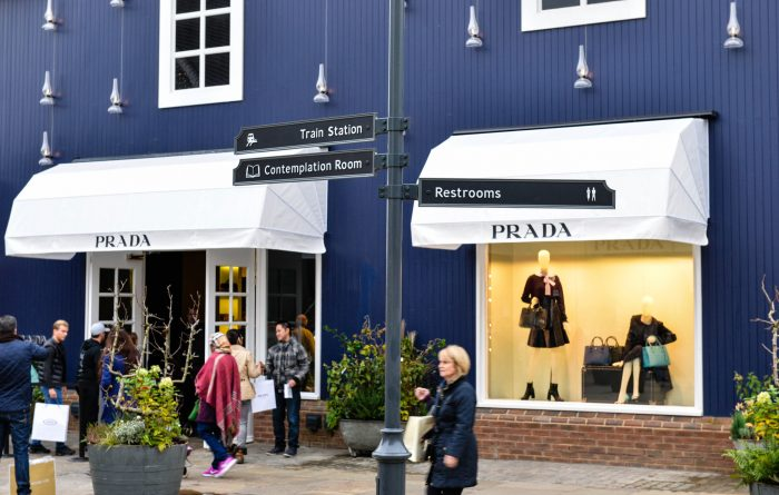 Bicester Village signage built by Octink featuring hand carved posts, cast aluminium finger blades and sign written messaging.