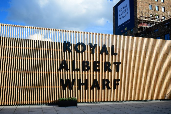 Image shows a cedar clad feature elevation with fret-cut letters at the Royal Albert Wharf marketing suite. Designed and built by Octink