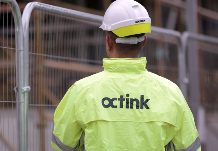 A site worker in a hiz-viz jacket with Octink printed on the back