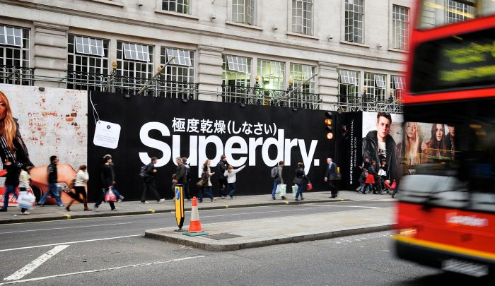 Advertising hoarding for Superdry in a busy London scene