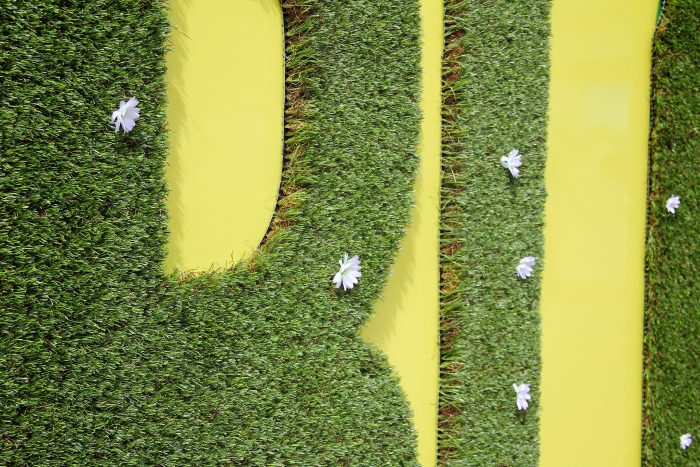 Close up of advertising sensory site hoarding with turf at Greenwich Peninsula by Octink