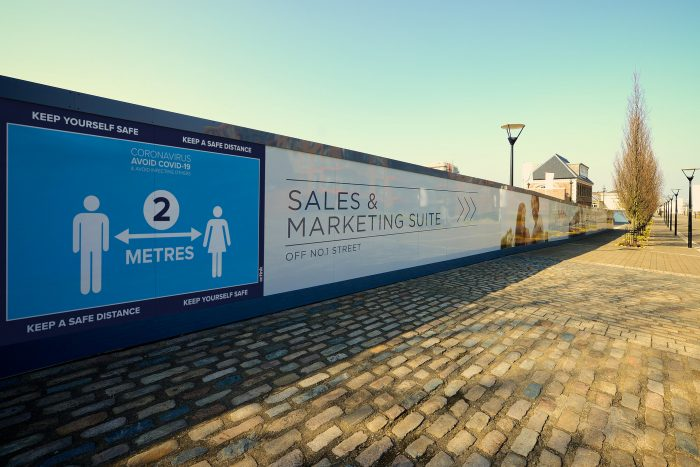 Advertising hoarding with social distancing message at the start of a housing development customer journey